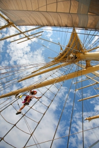 A passenger climbs up the rigging to the crows nest