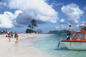 A tender decants guests on a beach in the Grenadines