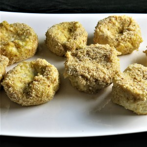 Savoury fish cakes dipped in egg and breadcrumbs await the deep fryer